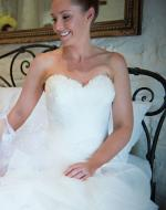 Draped tulle wedding dress with strapless neckline decorated with feathers